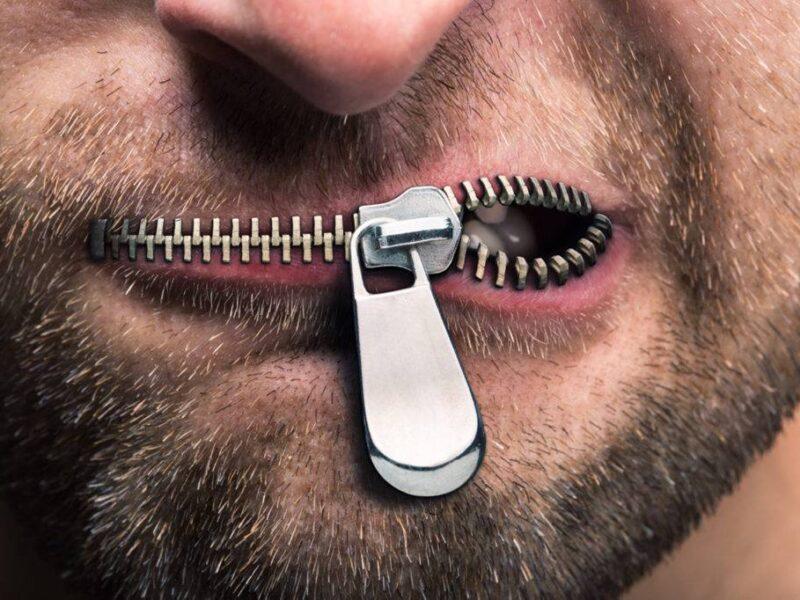 Hombre con boca cerrada por un cierre.