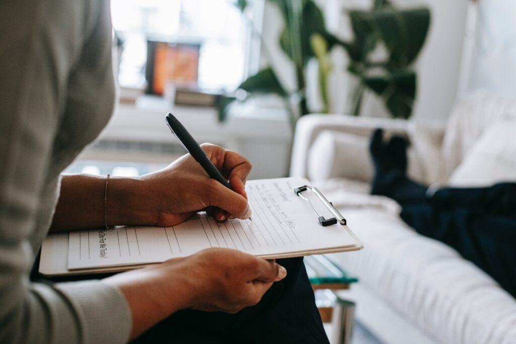 Psicólogo haciendo anotaciones de una terapia