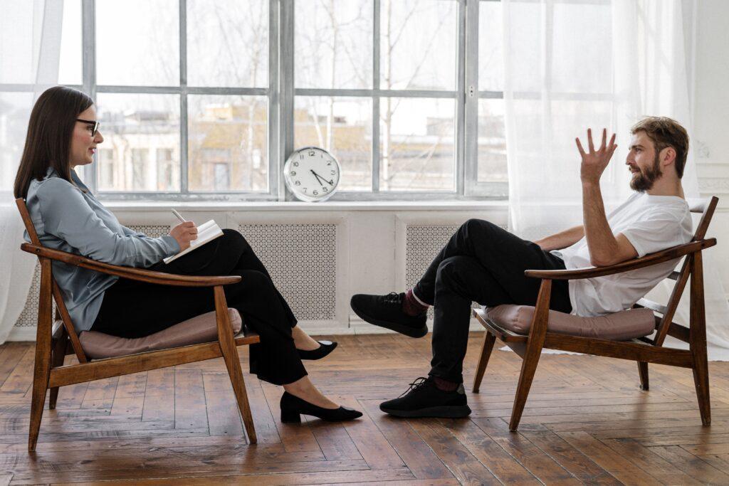Psicóloga dando terapia psicológica a un hombre